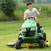 Yeong Il Noh, from Pusan South Korea, enjoys his first-ever ride on a lawn mower on friday during the Four States Farm Show in Pittsburg. Noh is serving a summer internship at Pittsburg State University.<br /> Globe | laurie Sisk <br /> Globe | Laurie Sisk
