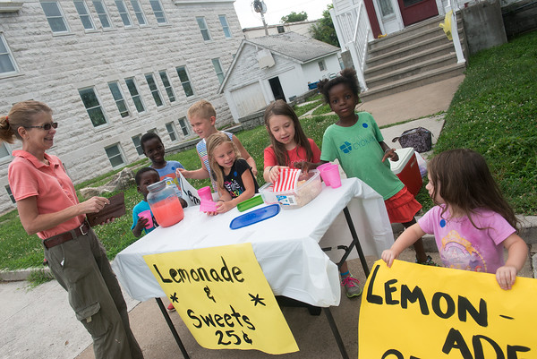 Globe/Roger Nomer<br /> (from left) Rose Dougless buys lemonade from her grandchildren Joshua Dougless, 3, Malachi Dougless, 8, Geyer Williams, 7, Emery Williams, 5, Gracelynn Dougless, 7, Karis Dougless, 6, and Kya Dougless, 3, on Friday in Carthage. The family was selling baked treats and lemonade as a summer acitivity.