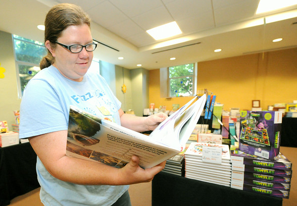 Mary Nicholas peruses items up for sale at the Carthage Library's Book Fair on Tuesday at the library.<br /> Globe | Laurie Sisk