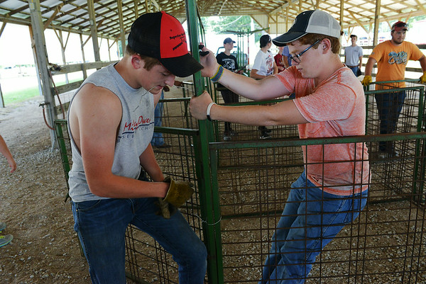 Globe/Roger Nomer<br /> Brett Robinson, 16, Sarcoxie, left, and Dayton Maneval, 16, Jasper, put together a pen at the Jasper County Fairground on Monday morning.