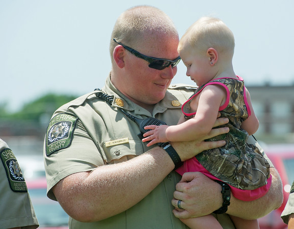 Globe/Roger Nomer<br /> Newton County Sheriff Deputy Chris Farmer holds his daughter Kinlee, 10 months, on Sunday at a rally to support law enforcement officers at the Lampo Building in Neosho. Leaders at the rally hoped to draw attention to the fact that officers have family members that support them.