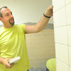 John Hefferman installs new tiles in one of the restrooms at Eastmoreland on Monday.<br /> Globe | Laurie Sisk