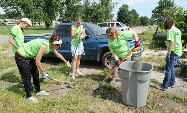 World Renew volunteers help clean tornado debris at a home near 15th street and East avenue in Baxter Springs on Wednesday.<br /> Globe | Laurie Sisk