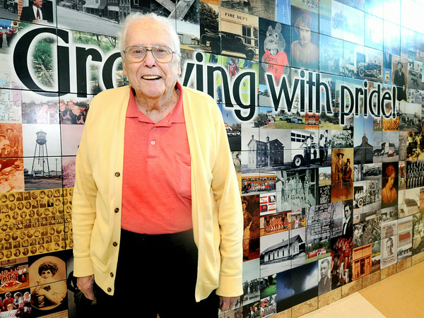 "Bob Miller, known to some as ""Mr. Carl Junction,"" poses in front of a mural depicting the history of the town on Tuesday at the Carl Junction Community Center.<br /> Globe 