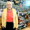 """Bob Miller, known to some as """"Mr. Carl Junction,"""" poses in front of a mural depicting the history of the town on Tuesday at the Carl Junction Community Center.<br /> Globe 