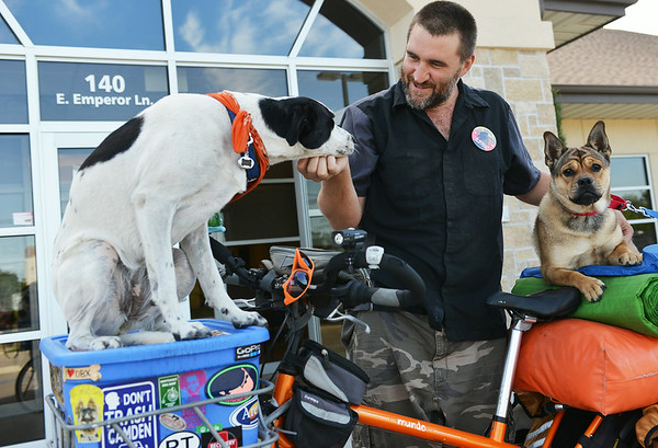 Globe/Roger Nomer<br /> Mike Minnuk introduces his dog Bixby, left, to Squishy, who is up for adoption at the Joplin Humane Society. Minnuk is traveling across the country by bicycle, highlighting local animals up for adoption.