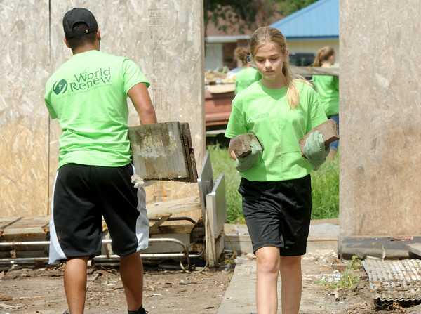 World Renew volunteers Brooke Janssen, 13, Norwalk, Iowa salvages useable brick as Nick Clark, Des Moines, Iowa  removes rubbish at a tornado damaged home at 1917 Park Street in Baxter Springs on Wednesday.<br /> Globe | Laurie Sisk