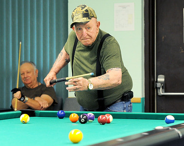 Don Gilleland watches his shot roll toward the hole as Richard Bible waits his turn on one of four pool tables at the Joplin Senior Center on Friday morning.  Globe | Laurie Sisk