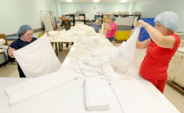 From the left: Joplin Workshop, Inc. employees Patsy Miller and Theresa McMillen fold towels for local hospitals in the laundry at the workshop on Tuesday afternoon.<br /> Globe | Laurie Sisk