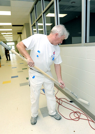 John Fast, of Fast Monks Painting, Springfield, touches up the painting inside a hallway of Carthage R-9's new intermediate school on Thursday.<br /> Globe | Laurie Sisk