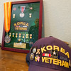 The reflection of Korean veteran Edwin Patron can be seen of a plaque containing some of the many medals Patron was awarded as part of his service. The medals are placed on a dresser in Patron's bedroom in the Jones' rural Verona home.<br /> Globe | Laurie Sisk