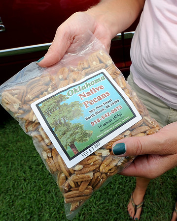 Holly Holton holds a pound bag of pecans produced on their Miami family farm.<br /> Globe | Laurie Sisk