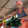 Globe/Roger Nomer<br /> Misty Phillips, Mulberry, Kan., stocks vegetables on Tuesday at the Webb City Farmers Market.