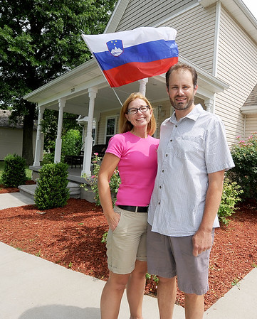 From the left: Gregor and Jasna Kalan stand outsdie their Chicopee home, where a Slovenian flag waves in the breeze on Friday. The couple and their four children celebrate both the U.S. Independence Day and Slovenia's Independence Day.<br /> Globe | Laurie Sisk