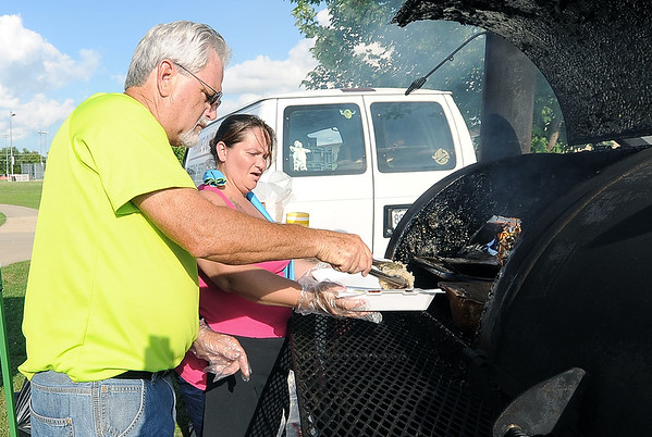 Rusty Boucher and Maleana Mertz, of Prime Cut Catering, serve an order of freshly grilled brats during the Joplin Independence Day Celebration on Monday at the Joplin Athletic Complex.<br /> Globe | Laurie Sisk