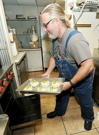 Jason Miller, owner of Instant Karma Gourmet Hot Dogs, places Brie en Croute topped with jalapenos into an oven in preparation for the day's ramen special on Friday. Miller was recently awarded Feast Magazine's Chef of the Year for Mid-Missouri.<br /> Globe | Laurie Sisk