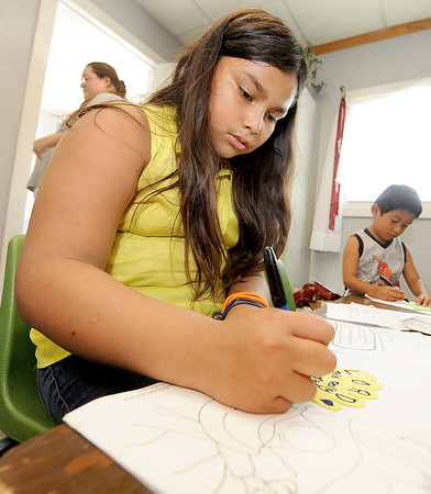 Nine-year-old volunteer Ruby Portillo leads an activity for younger children on Wednesday at Feeding Inc. in Carthage. Since transitioning from the former River Street Pantry, Feeding Inc. has expanded its programs to include language classes and teaching workplace skills.<br /> Globe | Laurie Sisk