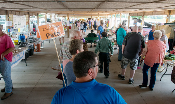 Globe/Roger Nomer<br /> George Thornton, Saginaw, holds a sign marking the end of the line for Pate's Orchard on Tuesday at the Webb City Farmers Market.