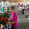 Globe/Roger Nomer<br /> Haley Phillips, 9, Mulberry, Kan., helps her mother prepare for the opening of the Webb City Farmers Market on Tuesday.
