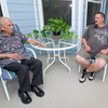 Korean War veteran Edwin Patron, left, sits with caretaker Tom Jones on a screened-in porch at Jones' rural Verona home on Friday. Jones said Patron, a former dance instructor, likes to practice his craft on the porch.<br /> Globe | Laurie Sisk