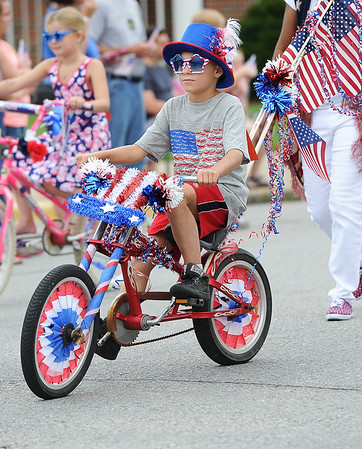 Nine-year-old Trenton Lewis rides his patriotic decorated bike in the Fourth of July Parade in downtown Carl Junction on Monday.<br /> Globe | Laurie Sisk