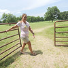 Holly Holton stands near the gate of the family's Miami pecan grove, where they produce Oklahoma Native Pecans. Holotn and her husband, Jim Holton, are subleasing land from Northeastern Oklahoma A&M under a Grand River Dam Authority program.<br /> Globe | Laurie Sisk