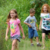 From the left: Seven-year-old Reaghan Hedrick, of Lee's Summit, Evan Collier, 6, of Raytown and Aurora Hedrick, 8, of Lee's Summit, walk along a path of wildflowers on Wednesday morning at Wildcat Park. The park will soon be celebrating its 100th anniversary.<br /> Globe | Laurie Sisk