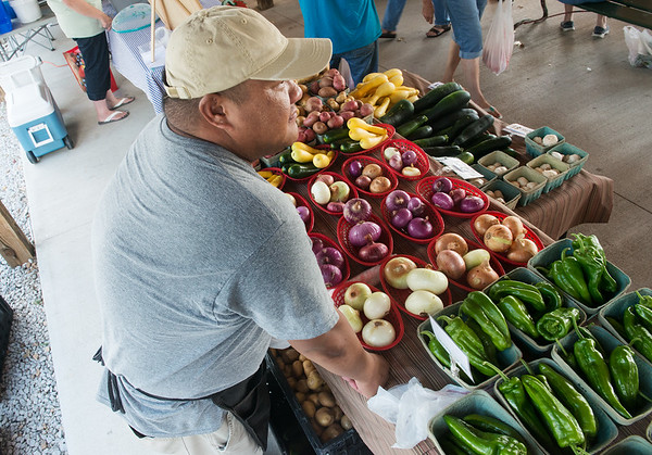 Globe/Roger Nomer<br /> Fue Yang, Rocky Comfort, waits for customers on Tuesday at the Webb City Farmers Market.