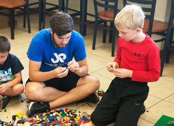 Globe/Roger Nomer<br /> Jaxon Meredith, rec instructor, helps Aidan Koch, 10, with a Lego creation on Tuesday during Lego Summer Camp at the Joplin Athletic Complex.
