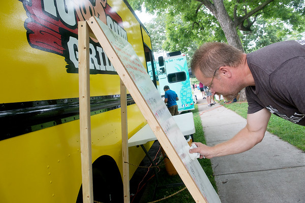 Globe/Roger Nomer<br /> David Healy, Carthage, works on his menu for Pig Out Grill on Friday before the food truck festival in Central Park in Carthage.