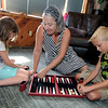 Chrys Corcoran, center, sets up a game of backgammon for her grandchildren. Anna Corcoran, 8, left  and Kylan Corcoran, 10 while caring for them in her Joplin home on Thursday.<br /> Globe | Laurie Sisk