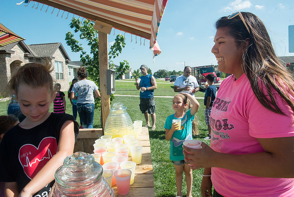 Globe/Roger Nomer<br /> Lexi Daniell, left, talks with Drew Yockey on Thursday at a lemonade stand to benefit Amanda Sharp. Daniell had Sharp for a third-grade teacher.