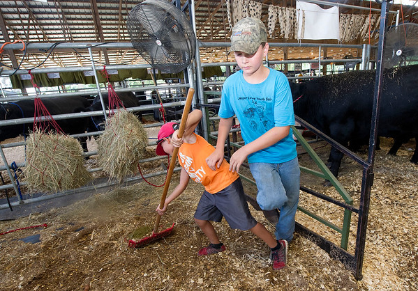 Seven-year-old Tyler Lambeth, left and Cody Peters, 13, help clean a friend's stall  on Wednesday at the Jasper County Youth Fair in Carthage. Peters is a member of the Avilla 4H Club.<br /> Globe | Laurie Sisk