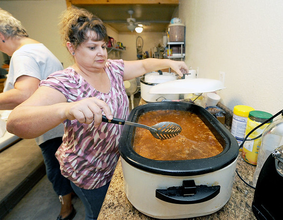 Volunteer Karen Brogan stirs a pot of beans on Wednesday at Feeding Inc. in Carthage. Since transitioning from the former River Street Pantry, Feeding Inc. has expanded its programs to include language classes and teaching workplace skills, while feeding about 2.000 people per month.<br /> Globe | Laurie Sisk