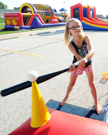 Xoey Cochran, 7, of Anderson, tests her skills at one of the inflatable games in the Kids' Zone during the Joplin Independence Day Celebration on Monday at the Joplin Athletic Complex.<br /> Globe | Laurie Sisk