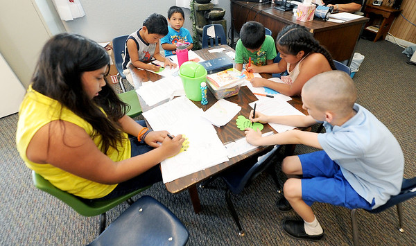 Nine-year-old volunteer Ruby Portillo, left,  leads an activity for younger children on Wednesday at Feeding Inc. in Carthage. Since transitioning from the former River Street Pantry, Feeding Inc. has expanded its programs to include language classes and teaching workplace skills.<br /> Globe | Laurie Sisk