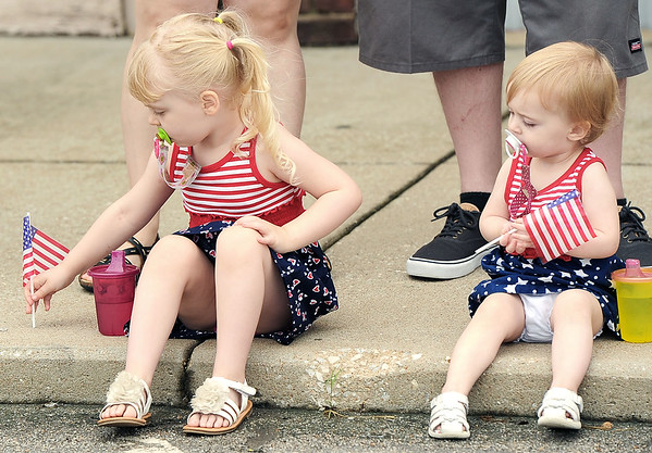 Three-year-old Brynlee Johnson, tries to plant her flag in a sidewalk as one-year-old sister Nora Johnson watches before the start of the Fourth of July Parade in downtown Carl Junction on Monday. The Johnsons are from Webb City.<br /> Globe | Laurie Sisk