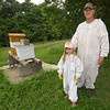 Six-year-old Lila Cade stands with her father, Ben Cade near her hives at their rural Carthage home on Wednesday night.<br /> Globe | Laurie Sisk