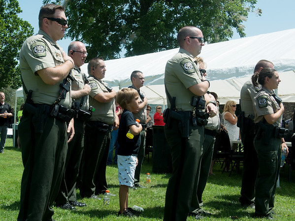Globe/Roger Nomer<br /> Raiden Engberg, 8, stands for the National Anthem with members of the Newton County Sheriff Department, including his father Dept. Rico Engberg, left, on Sunday at a rally to support law enforcement officers at the Lampo Building in Neosho.