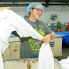 Joplin Workshop, Inc. employee Melissa Johnston separates sheets for ironing for local hospitals in the laundry at the workshop on Tuesday afternoon.<br /> Globe | Laurie Sisk
