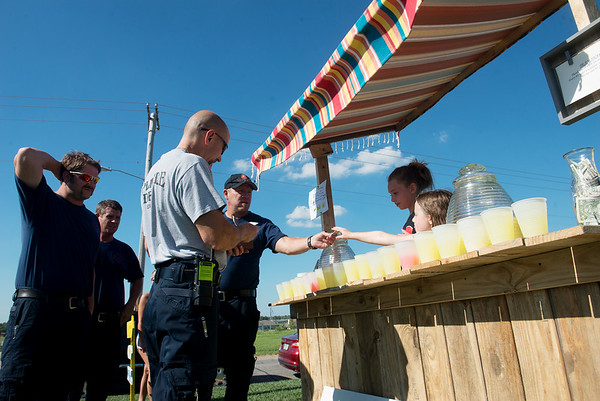 Globe/Roger Nomer<br /> Members of the Joplin Fire Department buy lemonade on Thursday at a stand benefiting Amanda Sharp.