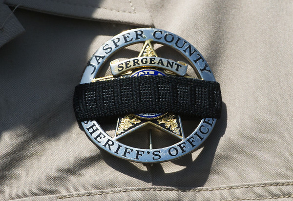 Globe/Roger Nomer<br /> A Jasper County Sheriff Department officer wears a black band on his badge to recognize those lost in recent violence on Sunday at a rally to support law enforcement officers at the Lampo Building in Neosho.