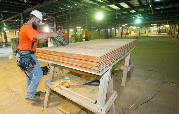 A worker saws panels for flooring Wednesday for the new Kansas City University of Medicine and Biosciences, which is slated to open next summer.<br /> Globe | Laurie Sisk