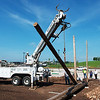 Globe/Roger Nomer<br /> Utility poles are installed at Mercy Park on Tuesday for Karl Lipscomb's public art sculpture. The sculpture is sponsored by the Cultural Affairs Committee with the Joplin Area Chamber of Commerce, and the poles were donated by Empire Electric.
