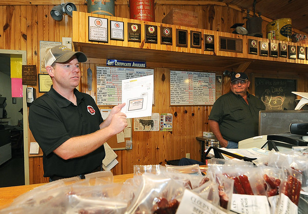 From the left: Andy Cloud talks about Cloud's Meats as owner Mike Cloud looks on during the 2016 7th District Agriculuture Tour on Friday in Carthage.<br /> Globe | Laurie Sisk