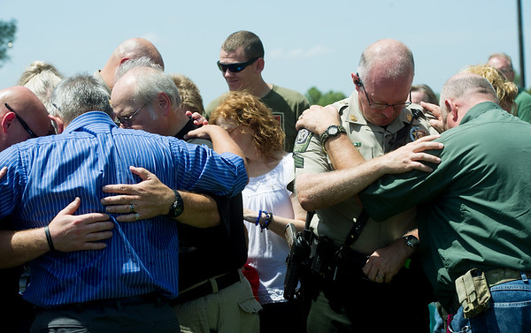 Globe/Roger Nomer<br /> Members of the public pray over officers on Sunday at a rally to support law enforcement officers at the Lampo Building in Neosho.