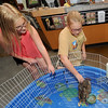 From the left: Nine-year-old Maddie Goetzinger and Natalie Goetzinger 12, both of Carthage, check out native Missouri fish in an aquarium at Wildcat Glades Conservation and Audubon Center on Wednesday morning.  The park will soon be celebrating its 100th anniversary.<br /> Globe | Laurie Sisk