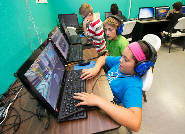 Front to back: Paris Romero, 11, Noah Lyons, 10 and Brayden Dick, 10, play computer games on Friday at the Boys and Girls Club of Southwest Missouri.<br /> Globe | Laurie Sisk