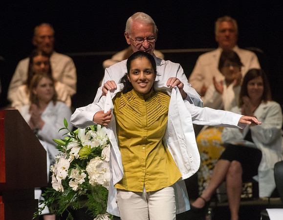 Globe/Roger Nomer<br /> Neha Bang, Joplin, receives her white coat from Larry McIntire during Monday's Kansas City University of Medicine and Biosciences White Coating Ceremony at Joplin High School.