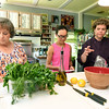 From the left: Brenda Spencer, Hailey Neighmond, 16 and Josie Mai assemble ingredients to begin working on their Mediterranean meal during a cooking class at Mai's Carthage home on Saturday.<br /> Globe | Laurie Sisk